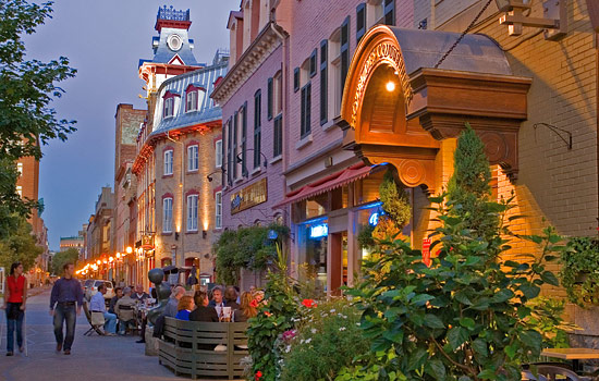 A street in Quebec lit up at dusk with people sitting outside