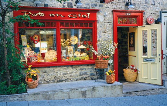 A Quebec City shop window with flower baskets outside