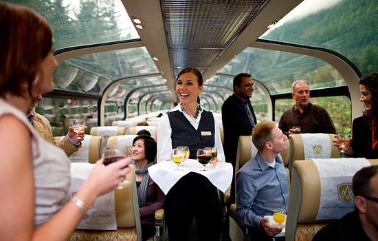 The gold leaf hostess serves passengers complimentary drinks on the Rocky Mountaineer