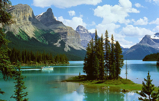 A boat cruises to Spirit Island on Maligne Lake with a Rocky Mountain backdrop