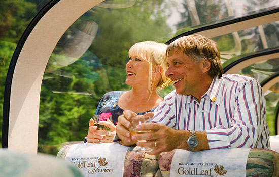 A couple enjoy complimentary drinks and views from the Rocky Mountaineer
