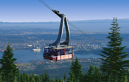 Passengers ride the Grouse Mountain gondola with views of Vancouver far below
