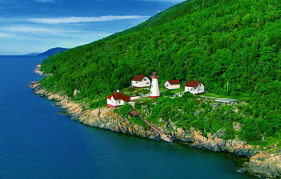 A lighthouse sits on the edge of a cliff in Quebec