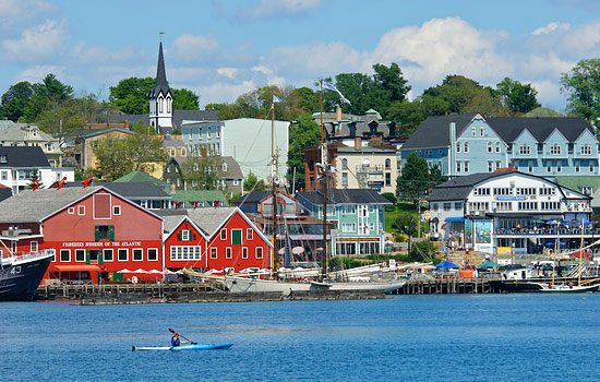 A kayaker passes by a clourful fishing town in Nova Scotia