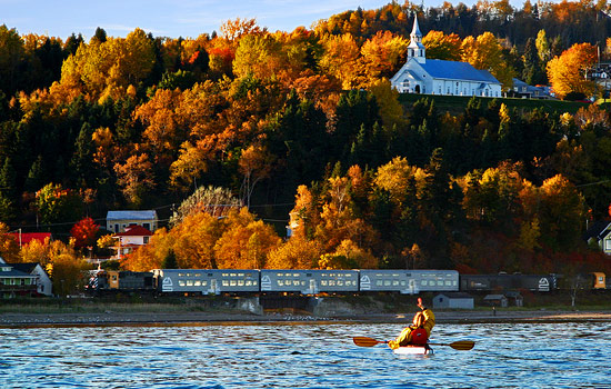 Kayaker waves to a passing train along the St. Lawrence river