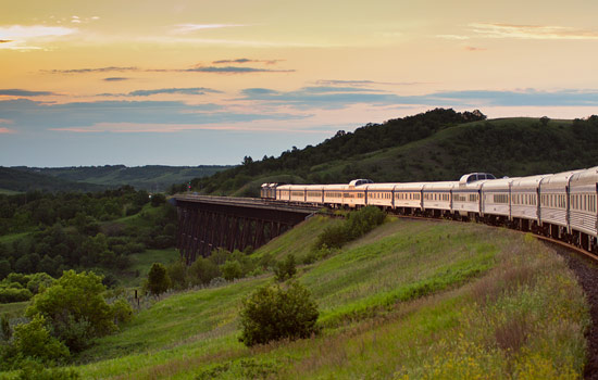 VIA Rail train passes over bridge at sunset