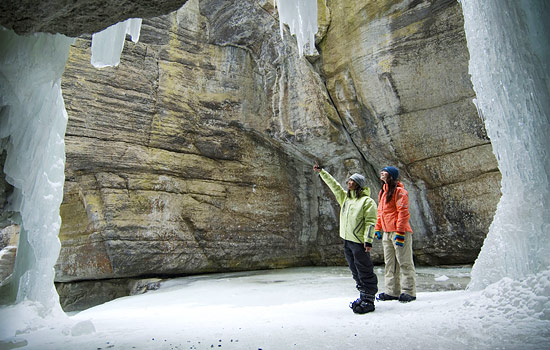 2 women on a Maligne Canyon ice walk stand below the rock formations and icefalls