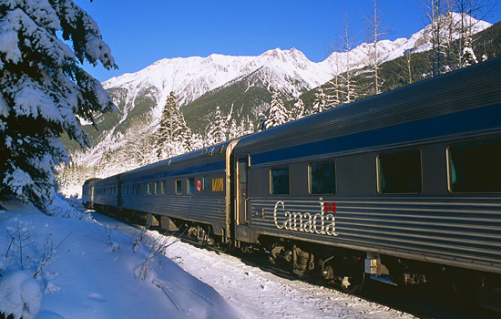 In a snow covered mountain valley the VIA Rail Canadian train travels by