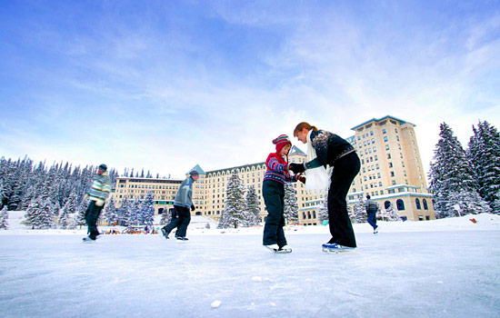 In front of the Chateau Lake Louise, guests ice skate on the frozen lake