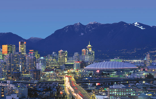 Downtown Vancouver lit up at night and distant mountain views
