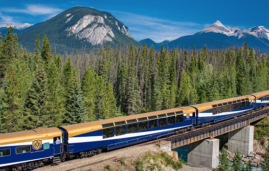 Passengers onboard the Rocky Mountaineer to Whistler admire the passing landscape from the outside viewing car