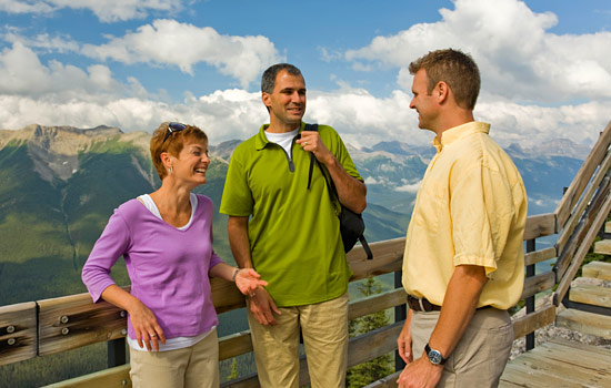 A small group tour enjoy views of the Canadian Rockies from a lookout point