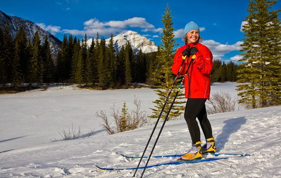 A young girl cross country skiing on snowy trails stops to take a break