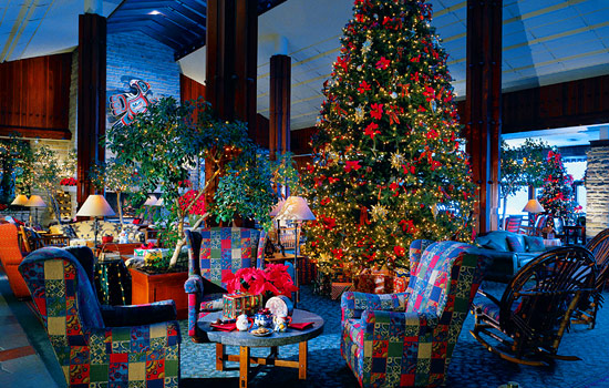 Sitting room of a hotel decorated for christmas with lights and a large christmas tree