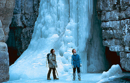 A couple of hikers explore the rock formations and icefalls on a tour of the Maligne Canyon in winter