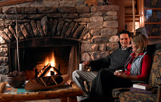 A couple enjoy warm drinks while sitting by a roaring fire