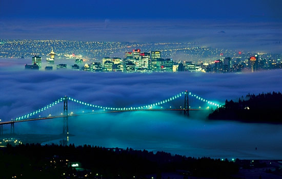 The Lions Gate Bridge stretches over a foggy Vancouver with the city lights twinkling in the distance